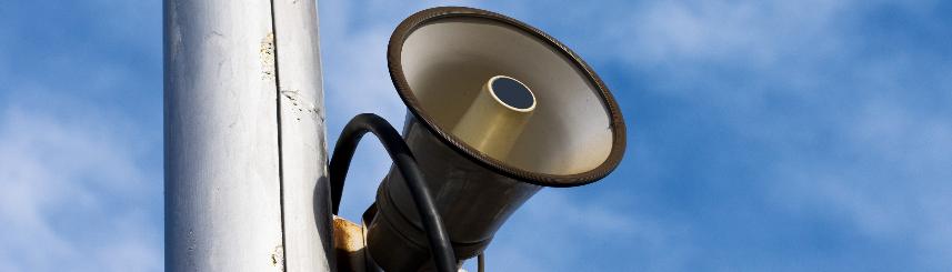Zdjęcie przedstawia syrenę alarmową przywieszoną na słupie, na tle nieba